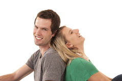 Молодые пары полагаясь спина к спине смеяться над Стоковое фото RF