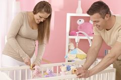 Молодые пары подготавливая детскую кроватку стоковая фотография