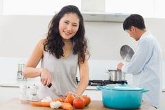 Молодые пары подготавливая еду совместно в кухне стоковые фото