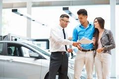 Молодые пары подписывая контракт в выставочном зале автомобиля Стоковые Изображения RF