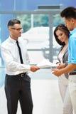 Молодые пары подписывая контракт в выставочном зале автомобиля Стоковые Фото