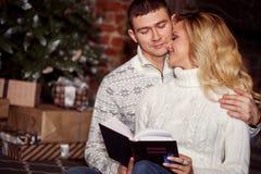 Молодые пары празднуя Новый Год дома Человек и женщина читая книгу совместно на предпосылке рождественской елки Стоковые Изображения RF