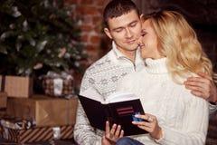 Молодые пары празднуя Новый Год дома Человек и женщина читая книгу совместно на предпосылке рождественской елки Стоковое фото RF