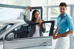 Молодые пары празднуя приобретение автомобиля в выставочном зале автомобиля стоковые фотографии rf