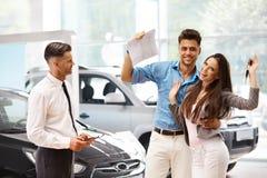 Молодые пары празднуя приобретение автомобиля в выставочном зале автомобиля стоковое изображение