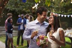 Молодые пары празднуя свадьбу с партией в задворк стоковая фотография rf