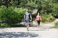 Молодые пары практикуя нордическую прогулку ` s стоковая фотография