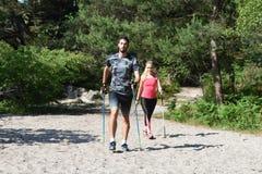 Молодые пары практикуя нордическую прогулку ` s стоковые фото
