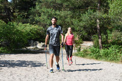 Молодые пары практикуя нордическую прогулку ` s стоковая фотография rf