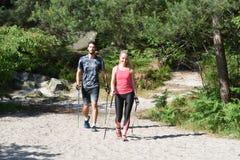 Молодые пары практикуя нордическую прогулку ` s стоковые изображения