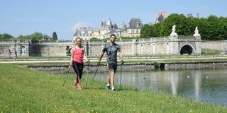 Молодые пары практикуя нордическую прогулку ` s стоковое изображение rf