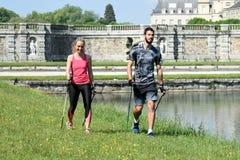Молодые пары практикуя нордическую прогулку ` s стоковое изображение