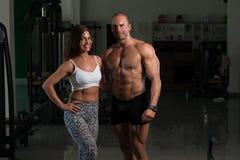 Молодые пары представляя в спортзале Стоковая Фотография
