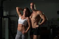 Молодые пары представляя в спортзале Стоковое Изображение
