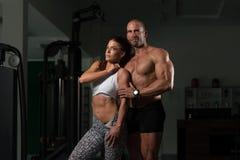 Молодые пары представляя в спортзале Стоковая Фотография RF