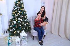 Молодые пары представляя на камере, одине другого объятия и целуя внутри Стоковые Фото