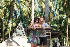 Молодые пары представляя около качания на тропическом пляже, остров Бали рая, Индонезия Солнечный день, счастливые каникулы внутр Стоковые Изображения