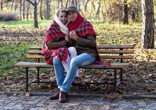 Молодые пары предусматриванные в шотландке сидя на стенде Стоковые Фотографии RF