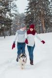 Молодые пары при осиплая собака идя в зиму паркуют, человек и женщина играя и имея потеху с собакой Стоковые Фото