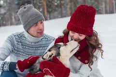 Молодые пары при осиплая собака идя в зиму паркуют, человек и женщина обнимая собаку Стоковое Фото