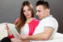 Молодые пары при таблетка сидя на кресле дома Стоковая Фотография