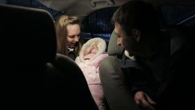 Молодые пары при newborn младенец сидя в автомобиле и говорить видеоматериал
