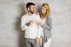 Молодые пары провозглашать с белым вином Стоковые Фото