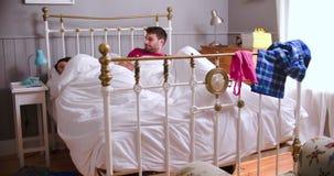 Молодые пары просыпая вверх в кровати и используя приборы цифров сток-видео