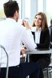 Молодые пары профессионалов беседуя во время coffeebreak стоковое изображение
