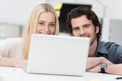 Молодые пары работая на компьтер-книжке дома Стоковое Изображение RF