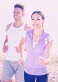 Молодые пары работая на пляже Стоковые Изображения RF