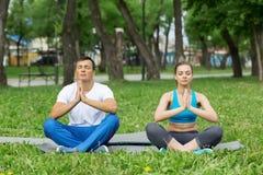 Молодые пары размышляя на зеленой траве Стоковое Изображение RF
