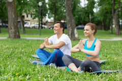 Молодые пары размышляя на зеленой траве Стоковые Фото