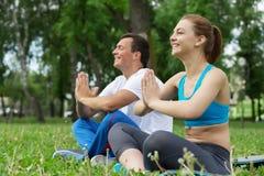 Молодые пары размышляя на зеленой траве Стоковое фото RF