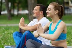 Молодые пары размышляя на зеленой траве Стоковые Фотографии RF