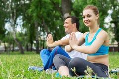 Молодые пары размышляя на зеленой траве Стоковые Изображения RF