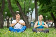 Молодые пары размышляя на зеленой траве Стоковое Изображение