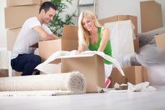 Молодые пары распаковывая или коробки упаковки Стоковая Фотография RF