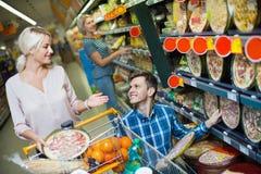 Молодые пары семьи выбирая охлаженную пиццу Стоковое фото RF