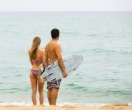 Молодые пары серферов на пляже Стоковая Фотография RF