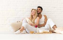 Молодые пары сидят на поле подушек, счастливом испанском человеке и любовниках подноса завтрака женщины в спальне Стоковая Фотография RF