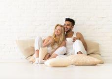 Молодые пары сидят на поле подушек, человеке счастливой улыбки испанском и любовниках женщины в спальне Стоковые Изображения