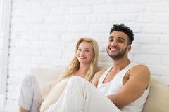 Молодые пары сидят на поле подушек, человеке счастливой улыбки испанском и любовниках женщины в спальне Стоковые Фотографии RF