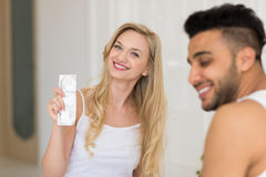 Молодые пары сидя в кровати, усмехаясь предохранение от контрацепции любовников презерватива владением человека женщины Стоковые Фото