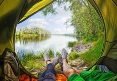 Молодые пары сидя в шатре пока смотрящ на реке Desna Стоковое Фото