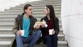 Молодые пары сидя на лестницах в городе видеоматериал