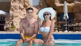 Молодые пары сидя на краю бассейна стоковое изображение