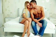 Молодые пары сидя на кровати Стоковое Изображение RF