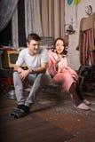 Молодые пары сидя на клетке на грязной комнате Стоковые Изображения