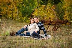 Молодые пары сидя на одеяле снаружи Стоковое Изображение RF